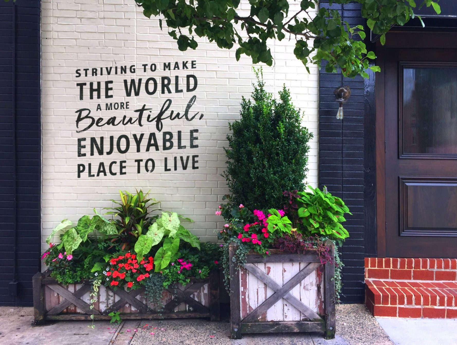"Colorful Summer Planters in front of a wall that says ""Striving to Make The World A More Beautiful, Enjoyable Place To Live"""